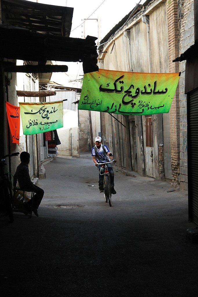 A boy is cycling in the alleys of the bazaar in Shiraz.